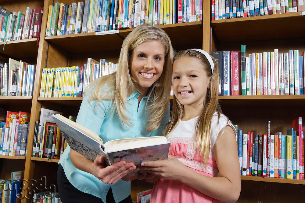 School girl and teacher holding book in library, portrait