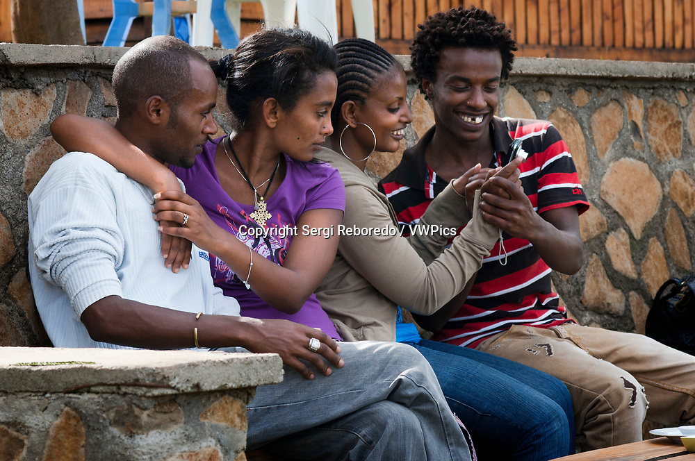 Young and fashion people, street scenery, Addis Abeba, Ethiopia. Two cosmopolitan couples from upper-class Ethiopians demonstrate that modernity has also reached these African lands. Ethiopia is the third fastest growing economy in the world
