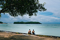 Two men sitting at a small beach near the Nusa Dua Blow Hole in Bali, Indonesia.