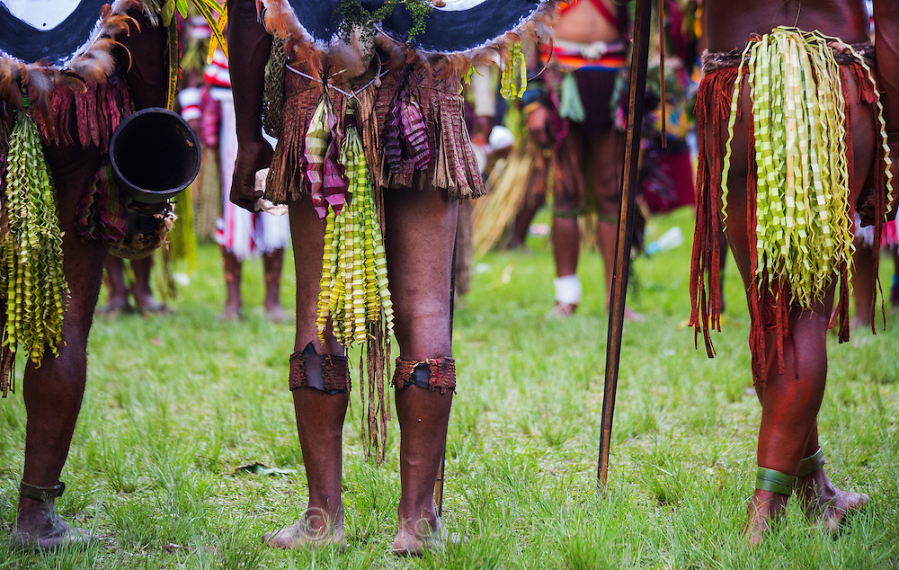 Low angle of a tribal group showing their ornamental skirts, crimped leaves spear and drum, Goroka Show, Papua New Guinea.