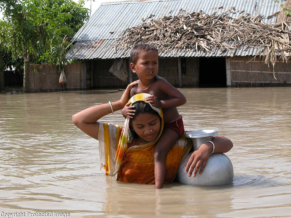 Flood victim Bangladeshi immigrant, Mussamed Fultara Khatun is carrying her child, Sahida Khatun (3) and going to collect drinkingwater after her house is submerged by floodwaters at Birshing village, about 319 kilometers southwest of Gauhati, capital of northeastern Indian state of Assam, Wednesday, July 14, 2004. .Floodwaters of the Asia's one of the largest river, Brahmaputra and its 35 tributaries have affected more than one million in all of Indian subcontinent and disrupted communication in many parts of the India and Bangladesh, sources said. (AP Photo/ Shib Shankar Chatterjee).