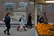 A lady carries a spotted shopping bag past fresh oranges on sale at a stall on London Bridge during the evening rush-hour, from the City southwards to Southwark, on 3rd May, in London, England