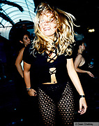 Girl dancing wearing black tights and a criss cross top in Ibiza 1999
