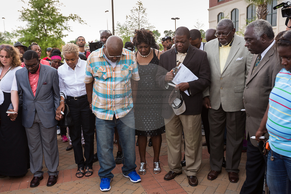 People hold hands during a moment of silence during a vigil outside the North Charleston City Hall following the shooting death of Walter Scott April 10, 2015 in Charleston, South Carolina. Scott was shot multiple times by police after running from a traffic stop.