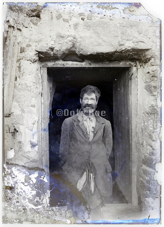 man dressed in tattered clothing standing on door opening on old eroding glass plate
