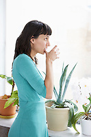 Businesswoman drinking and looking through window by pot plants