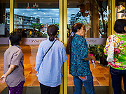 09 NOVEMBER 2018 - BANGKOK, THAILAND: Women waiting to get into ICONSIAM look through the door into the mall before the grand opening. ICONSIAM opened November 9. ICONSIAM is a mixed-use development on the Thonburi side of the Chao Phraya River. It includes two large malls, with more than 520,000 square meters of retail space, an amusement park, two residential towers and a riverside park. It is the first large scale high end development on the Thonburi side of the river and will feature the first Apple Store in Thailand and the first Takashimaya department store in Thailand.     PHOTO BY JACK KURTZ