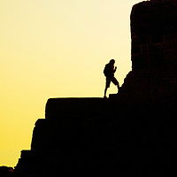 Silhouette of a young man standing against a suntet on a stone jetty at Brighton England