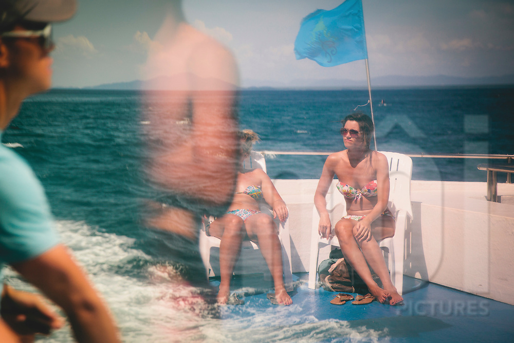 Caucasion females sunbathing on a boat's deck, Ko Phi Phi Don, Thailand, Southeast Asia
