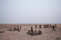 © Licensed to London News Pictures. 11/09/2015. Kirkuk, Iraq. Kurdish peshmerga fighters wait in a sandy field for the beginning of an offensive to expand a safety zone around the city of Kirkuk, Iraq.<br /> <br /> The offensive, which went unchallenged after ISIS left the area ahead of the attack, saw the peshmerga capture 15 villages along the Kirkuk front line. The objective of the offensive was to expand the safety zone around Kirkuk, stopping militants from firing missiles and rockets in to the city of Kirkuk. 3 peshmerga were killed and 24 wounded due to improvised explosive devices left behind by the militants. Photo credit: Matt Cetti-Roberts/LNP