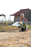 Young woman walking on road after surfing. Mexico.
