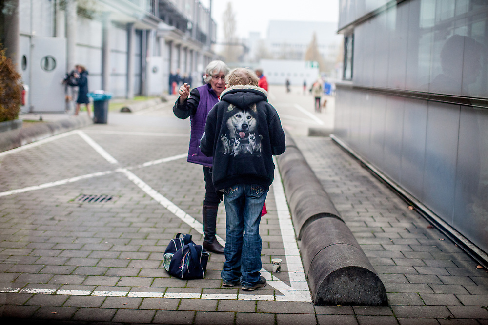 Participants discussing dog issues at the Leipzig Trade Fair outside facilities, one of them wearing a jacket with Husky portraits. Over 31,000 dogs from 73 nations will come together from 8-12 November 2017 in Leipzig for the biggest dog show in the world.