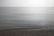 Grey calm water of the North Sea with gentle waves on a still day, from Shingle Street, Suffolk, England