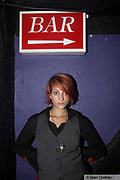 A young girl stood beneath a sign for the bar, Last ever 'Junk' club, Southend, UK 2006