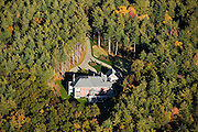 This large single-family home, hidden in a densely forested area, was built on real estate speculation for an upscale market.