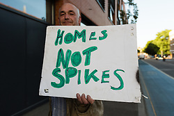 © Licensed to London News Pictures. 10/06/2014. London, UK. A demonstrator outside 118 Southwark Bridge Road in South East London, where controversial inch high metal spikes have been installed outside a luxury block of London flats to deter homeless people from sleeping in the doorway. Photo credit : Vickie Flores/LNP