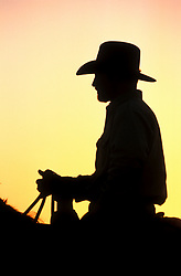 silhouette profile of a cowboy riding a horse at sunset
