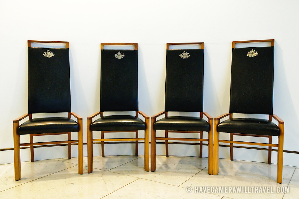 Chairs with the Australian coat of arms in gold on black leather in Australian Parliament House Canberra.