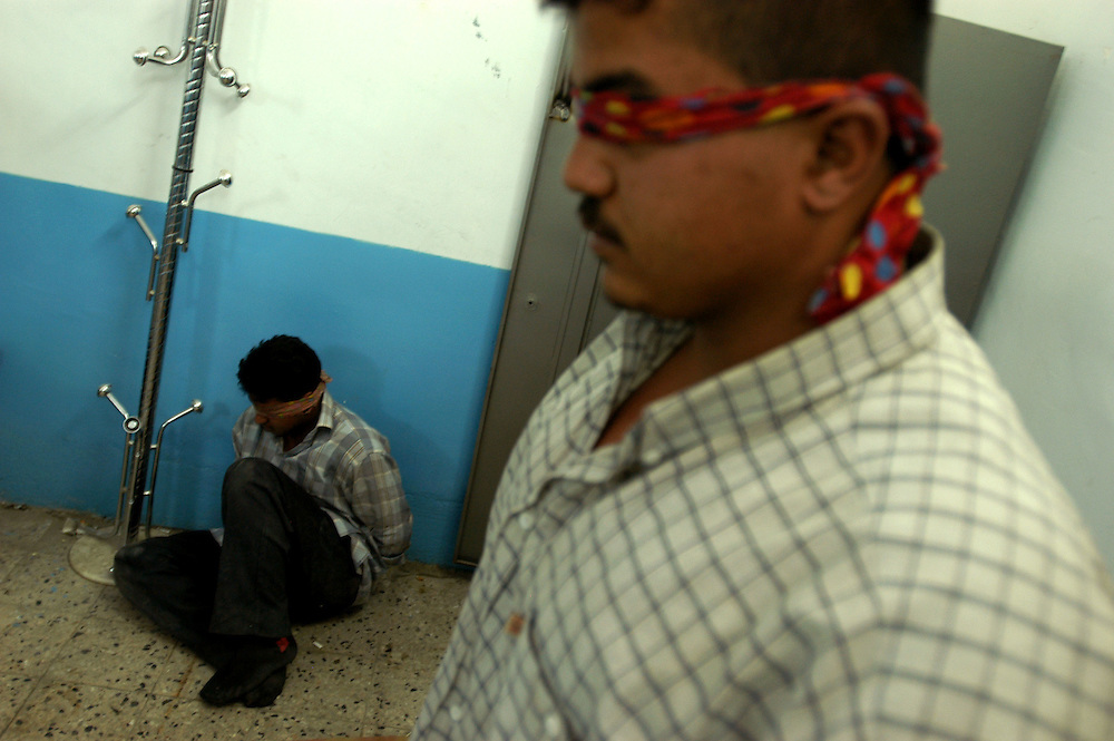 Blindfolded prisoners, who police say worked for the Iraqi National Congress leader Ahmed Chalabi and who are accused of armed robbery and murder, being held at a police station..Baghdad, Iraq. 24/04/2004.Photo © J.B. Russell