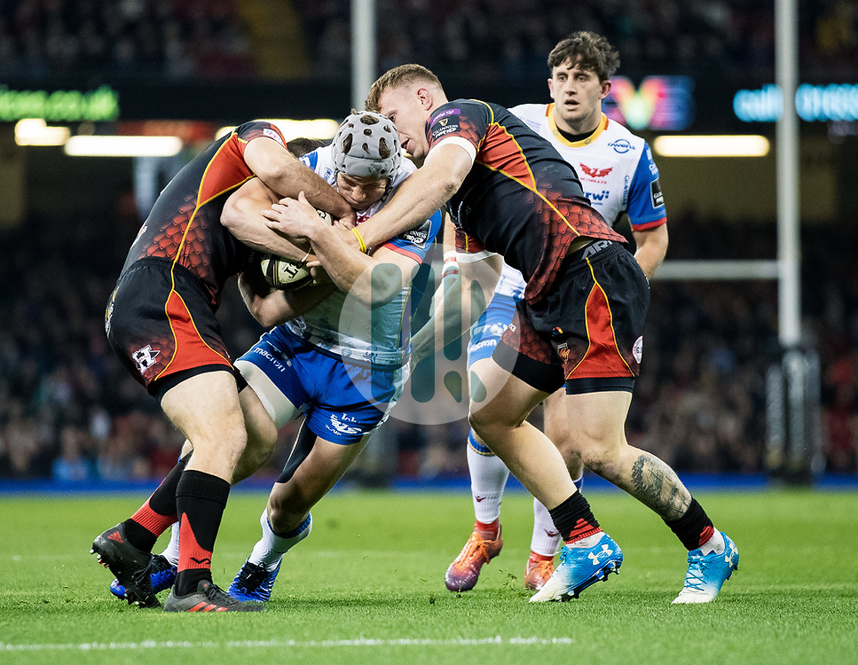 Jonathan Davies of Scarlets Adam Warren of Dragons<br /> <br /> Photographer Simon King/Replay Images<br /> <br /> Guinness PRO14 Round 21 - Dragons v Scarlets - Saturday 27th April 2019 - Principality Stadium - Cardiff<br /> <br /> World Copyright © Replay Images . All rights reserved. info@replayimages.co.uk - http://replayimages.co.uk