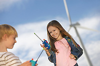 Boy and girl (5-9) playing with walky-talkies at wind farm