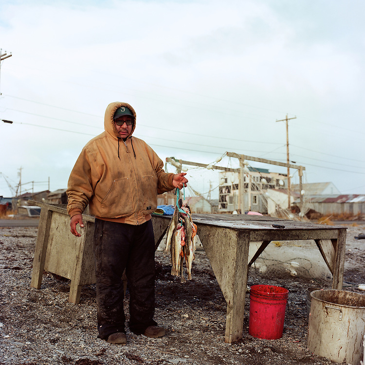 """Hardly anyone does this anymore. In the fall time they run thick—right now they are really healthy. We eat them half dried and frozen. I grew up eating this food."" — Nick Topkok preparing his day's catch of tomcod fish for dying, on the beach in Teller, Alaska."