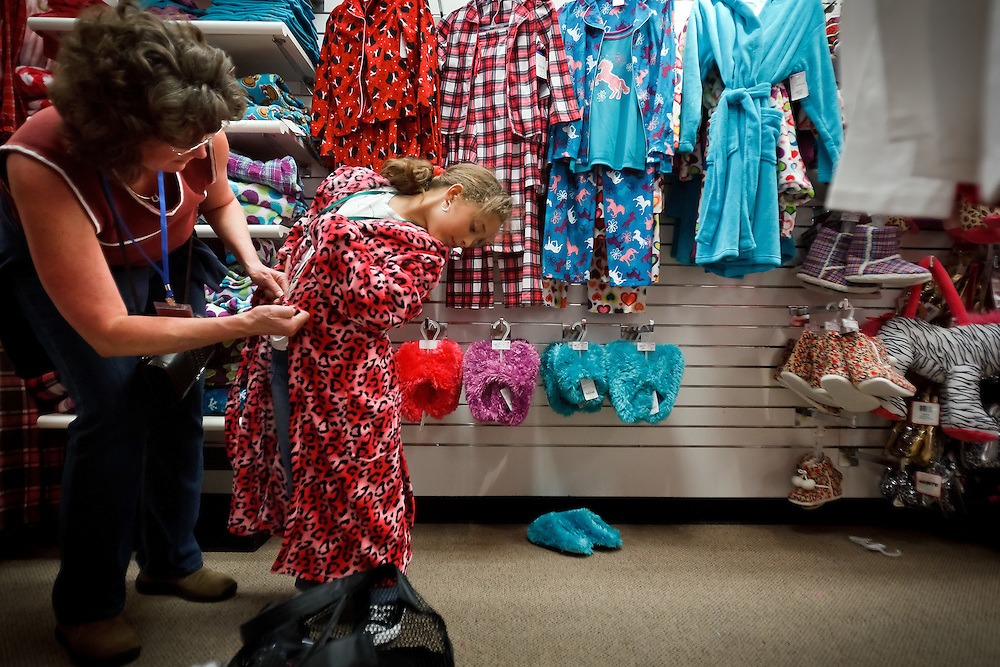"Tracie Anderson assists Sydney Adams, 7, with fitting a robe the Rathdrum girl picked out during the Kroc Center's ""Clothe-A-Child"" shopping spree Friday. Over two days, 120 children from seven area elementary schools were given $120 to purchase clothing at JCPenney in Coeur d'Alene."