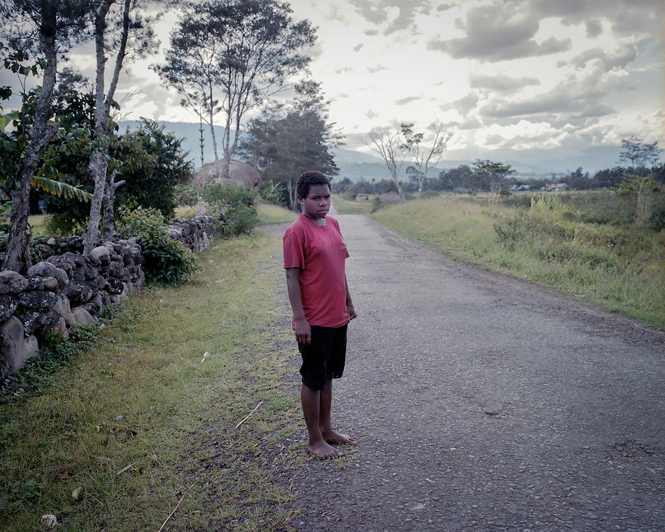 A teenager walking home in Wamena.<br /> <br /> Rough terrain, lack of transportation means, and the high cost of fuel and transportation are some of the biggest obstacles for people with HIV/AIDS to overcome in order to reach health facilities to get necessary care and medication.  Most Voluntary Counseling and Testing (VCT) clinics and ARV medication are available only in cities that are hundreds of miles away from villages.