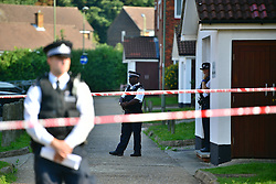 © Licensed to London News Pictures. 15/09/2016. London, UK. Police stand at the entrance to a flat which was the scene of a double shooting in a block of flats in East Finchley. Police were called by London Ambulance Service at 06:25hrs this morning to reports of two people injured at an address in north London. A man and a woman were found with gunshot injuries. Both were pronounced dead at the scene. Photo credit: Ben Cawthra/LNP