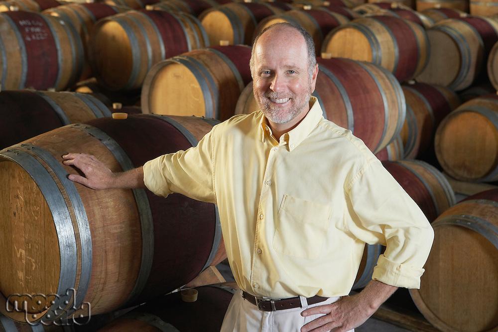 Man leaning on wine casks