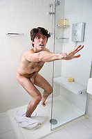 Scared naked man stopping someone in bathroom