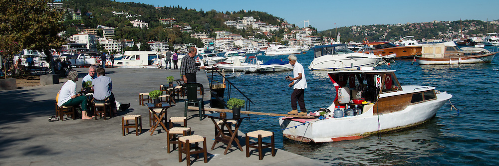 This elderly man walks the plank to serve tea dockside from his small boat.