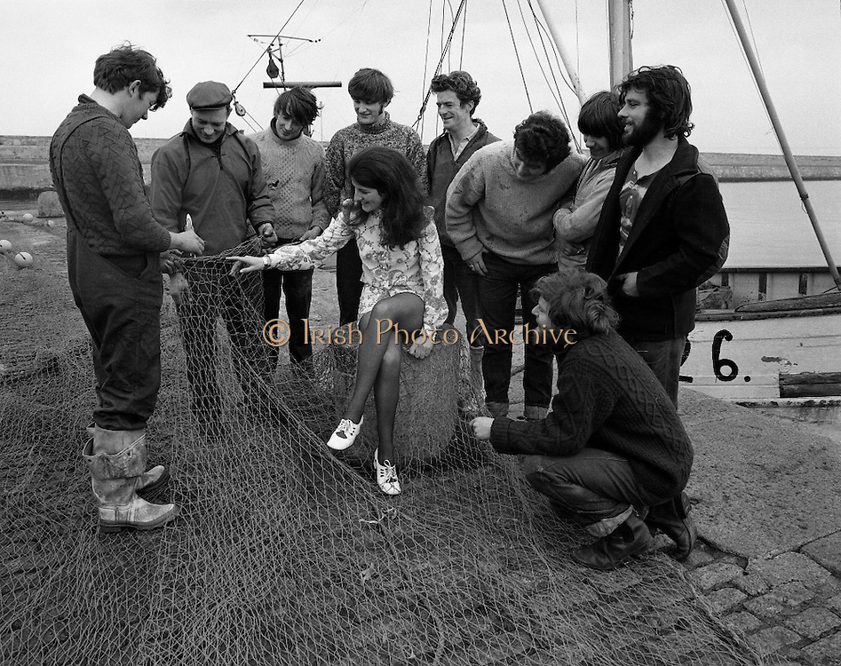 """Miss """"World Fishing"""" 1971..1971..13.03.1971..03.13.1971..13th March 1971..To present the more glamorous side of the fishing industry B.I.M. (Bord Iascaigh Mhara) organised a Miss World style competition for young women within the fishing industry.The winner, selected from six finalists from fishing ports around the country, will represent B.I.M. at the forthcoming World Fishing Exhibition to be held in Ireland. The winner will receive an all expenses paid trip to Paris for two courtesy of Normandy Ferries and a complete ensemble from """"Open Till Eight"""" fashions..Pictured on the harbour wall at Dun Laoghaire,""""Miss World Fishing"""" Ms Ann Scallan is surrounded by local fishermen."""