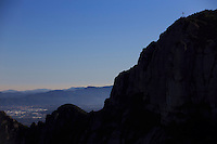 A Christian cross sits atop a large cliff on Mount Montserrat on the outskirts of Barcelona, Spain