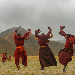 Monks making music and practising religious dances at a monastery in Tibet.