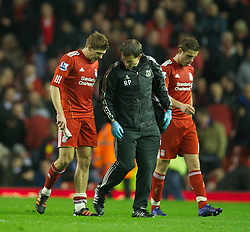 LIVERPOOL, ENGLAND - Tuesday, March 13, 2012: Liverpool's captain Steven Gerrard limps off the pitch with an injury at half-time as he talks to senior physiotherapist Rob Price during the Premiership match against Everton at Anfield. (Pic by David Rawcliffe/Propaganda)