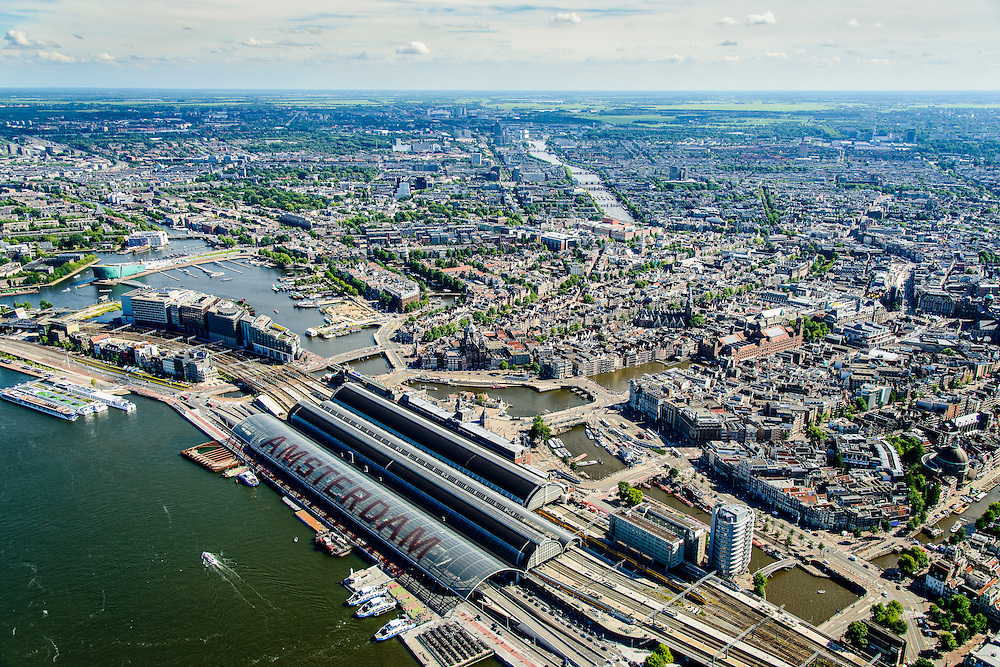 Nederland, Noord-Holland, Amsterdam, 01-08-2016; IJ-oever met nieuwe overkapping Amsterdam CS centraal station (busstation). Oosterdok, overzicht Amsterdamse binnenstad  en Amsterdam-Oost. Rivier de Amstel.<br /> Amsterdam Central Station and overview inner city with canals.<br /> <br /> luchtfoto (toeslag op standard tarieven);<br /> aerial photo (additional fee required);<br /> copyright foto/photo Siebe Swart