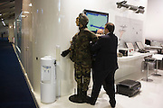 Exhibitors prepare mannequin soldier on their stand at the Farnborough Airshow.