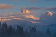 The high peaks of the Tetons are veiled by clouds at sunset in the Teton Valley, Idaho.