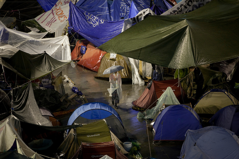 A woman walks through the tents during a protest camp in Madrid's Puerta del Sol, Monday, June 6, 2011.Tens of thousands of mostly young people have set up around-the-clock protest camps in cities and town across Spain since May 15 to complain about the government's handling of the economic crisis and what they see as a corrupted political party system.
