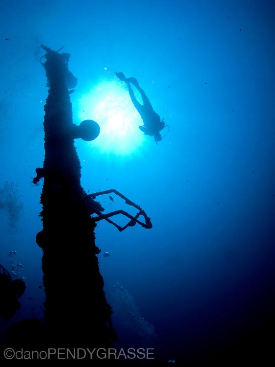 A diver floats above the mast of the El Aguila wreck in Roatan, Honduras.
