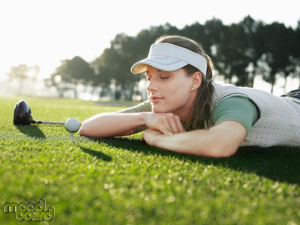 Young female golfer lying on court looking at ball on tee