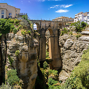 "Ronda Panoramic view over Puente Nuevo (""New Bridge"") The newest and largest of three bridges that span the 120-metre (390 ft)-deep chasm that carries the Guadalevín River and divides the city of Ronda, in southern Spain. Built between 1759-1793, the architect was José Martin de Aldehuela."