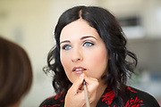 bride with blue eyes having makeup applied