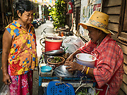 07 APRIL 2016 - BANGKOK, THAILAND: A vendor goes door to door selling cooked rice and curries in the squatters' community behind the walls in Mahakan Fort. Mahakan Fort was built in 1783 during the reign of Siamese King Rama I. It was one of 14 fortresses designed to protect Bangkok from foreign invaders, and only of two remaining, the others have been torn down. A community developed in the fort when people started building houses and moving into it during the reign of King Rama V (1868-1910). The land was expropriated by Bangkok city government in 1992, but the people living in the fort refused to move. In 2004 courts ruled against the residents and said the city could take the land. The final eviction notices were posted last week and the residents given until April 30 to move out. After that their homes, some of which are nearly 200 years old, will be destroyed.       PHOTO BY JACK KURTZ