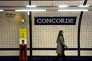 Paris, France, December 12, 2005-A woman walks through the Concorde metro station. It is named after the nearby Place de la Concorde. It is distinctive due to its décor; the tunnel for line 12 is decorated with tiles spelling the Déclaration des Droits de l'Homme et du Citoyen.