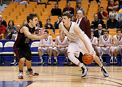 Wheeling Central guard Chase Harler (14) cuts the lane for two points during a semi final round game at the Charleston Civic Center.