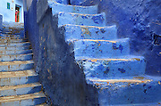 2 flights of steps painted blue in the medina or old town of Chefchaouen in the Rif mountains of North West Morocco. Chefchaouen was founded in 1471 by Moulay Ali Ben Moussa Ben Rashid El Alami to house the muslims expelled from Andalusia. It is famous for its blue painted houses, originated by the Jewish community, and is listed by UNESCO under the Intangible Cultural Heritage of Humanity. Picture by Manuel Cohen