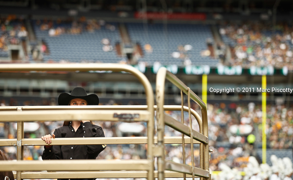 SHOT 9/17/11 1:31:53 PM - A female Ralphie Handler watches the crowd while waiting to run Colorado's mascot back onto the field after halftime against Colorado State during the Mile High Showdown game at Sports Authority Field at Mile High Stadium. Colorado won the in-state rivalry game 28-14. (Photo by Marc Piscotty /  © 2011)