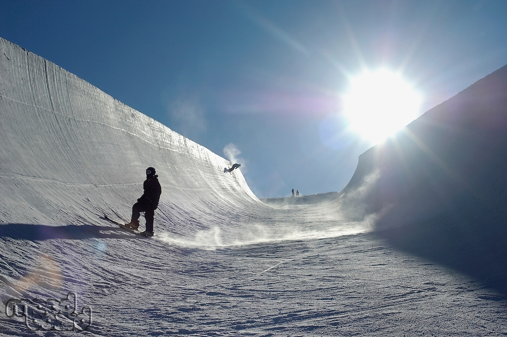 Silhouette of teenage snowboarder on halfpipe